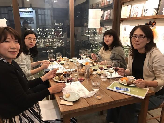 カフェ・ケープルヴィルのテーブルを囲んでワイングラスを片手に歓談する参加者の女性達