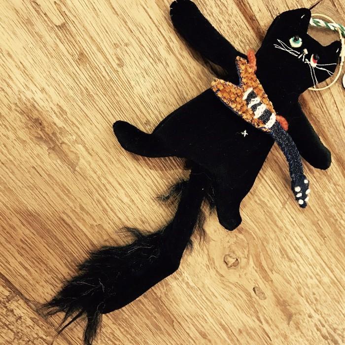 黒ネコ、しっぽがふさふさ。良く見ると肩からギターが。ギター弾きの猫!東京都・文京区千駄木のカフェ、ケープルヴィルで販売中。早い者勝ち。