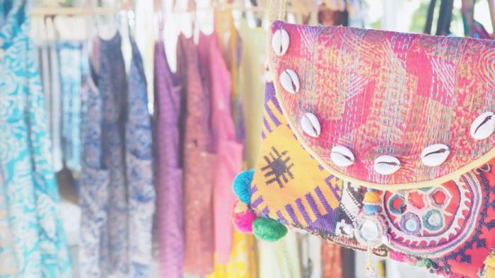 色とりどりの布を使った小物や洋服などが飾られているマーケットの店頭