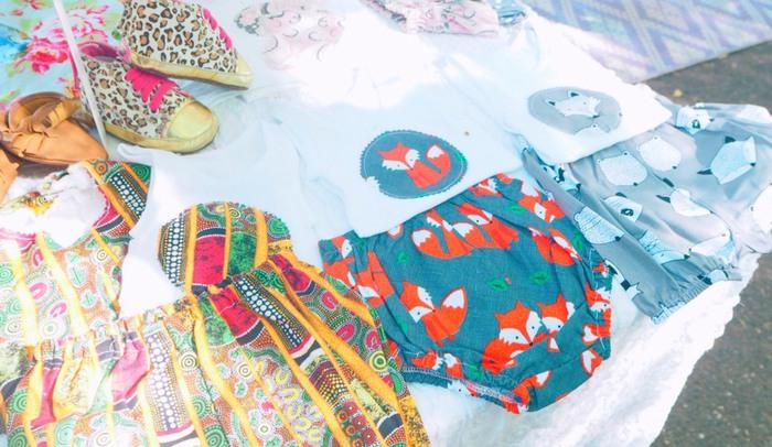 布地の柄が可愛らしいベビー服をファーマーズマーケットで飾っている様子