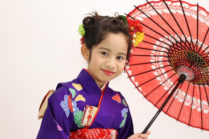 唐傘を回しながら、すこし気取ってお着物でポーズする7歳の女の子。七五三が嬉しいという表情。