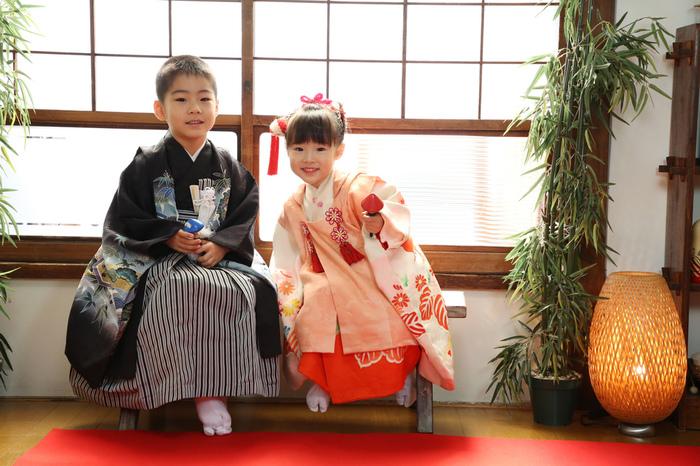 東京都文京区千駄木の古民家写真館ケープルヴィルのフォトスタジオで、3歳と5歳の七五三の衣装をきた兄弟が窓際に座っていて、たのしそうに写真を撮っているようす。