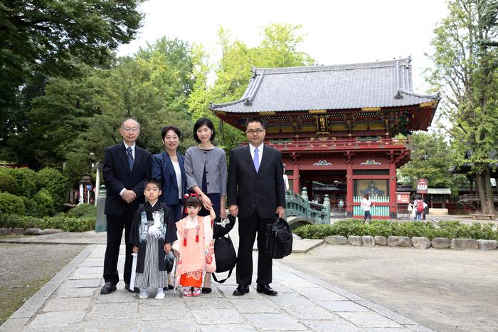 根津神社の境内で、おじいちゃん、おばあちゃん、ご両親、おこさまが全員集合して記念撮影。東京都文京区千駄木のケープルヴィル写真館のフォトグラファーは、出張撮影もいたします。