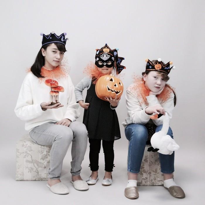 シュールなハロウィーンの仮装写真。かぼちゃと一緒に3人の女の子たち。