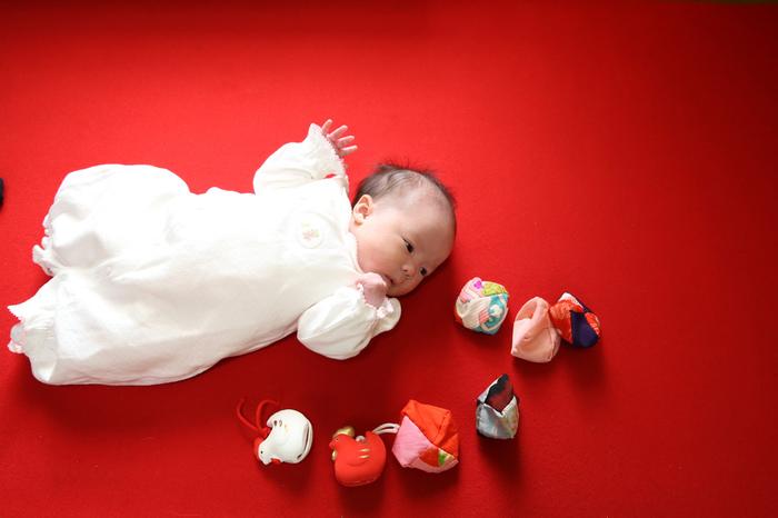 赤い毛氈の上で、ばたばたをカラダを動かしたり、おかあさんやお父さんの声に反応しながらお写真撮影のあかちゃん。