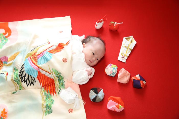東京都文京区千駄木の写真館、ケープルヴィルでは紅い毛氈の上で、お宮参りの産着のきものをかけて、お守りを置いてかわいらしい赤ちゃんのベビーフォト撮影。