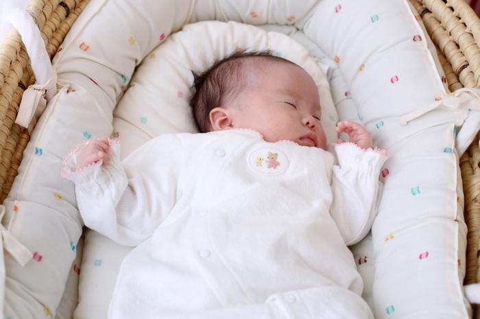 すやすやと眠るあかちゃん。ケープルヴィル2Fの写真スタジオでみんなに見守られてのお宮参り撮影。